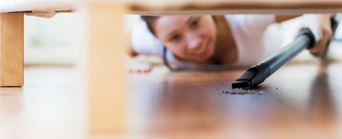 woman vacuuming a hard to reach spot under a couch