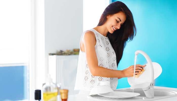 Woman moisturizing hands by washing dishes in home.